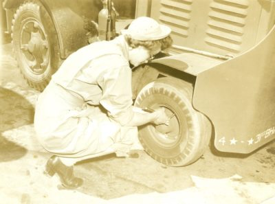 Tightening lug nuts in the motor pool at March Field. Note the WAC oxfords.
